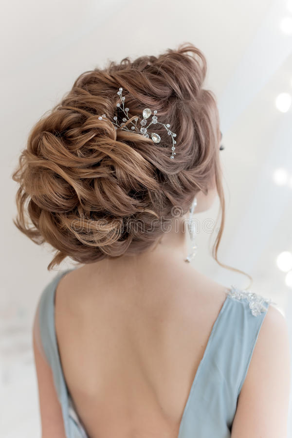 Beautiful volume hairstyle for a bride in a gentle blue light dress with large earrings and adornment in hair royalty free stock images