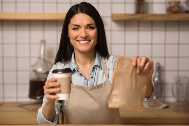 Waitress holding coffee to go and take away food. Beautiful waitress holding coffee to go and take away food in cafe and looking at camera stock photo
