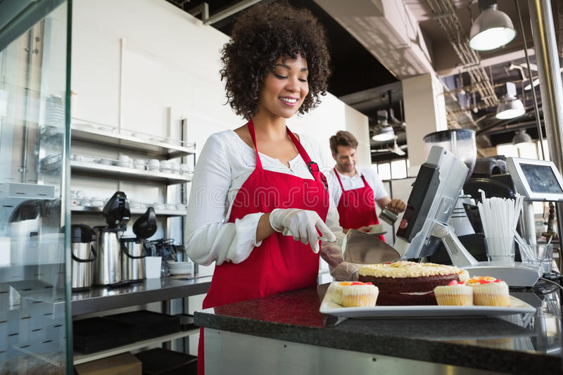 Beautiful waitress in red apron slicing cake stock images