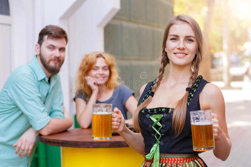 Beautiful waitress in traditional german costume holding beer glass in the bar. Smiling Pretty waitress in german octoberfest suit posing with two beer glasses royalty free stock photos