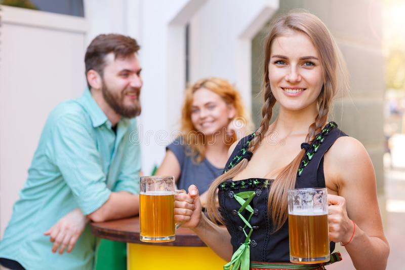 Beautiful waitress in traditional german costume holding beer glass in the bar. Smiling Pretty waitress in german octoberfest suit posing with two beer glasses stock photos