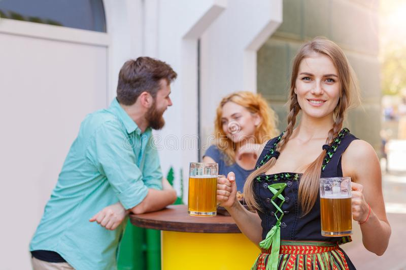 Beautiful waitress in traditional german costume holding beer glass in the bar. Smiling Pretty waitress in german octoberfest suit posing with two beer glasses royalty free stock images