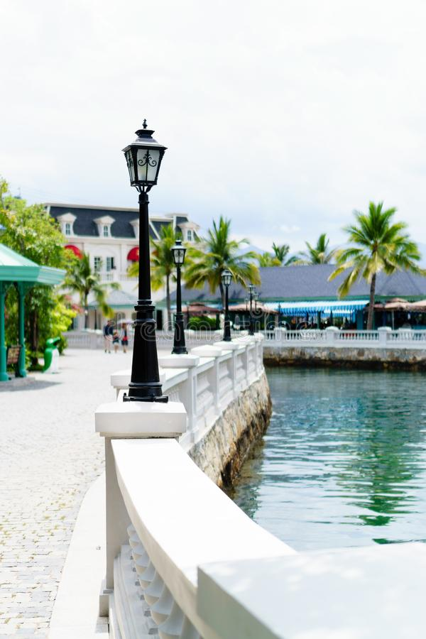 Beautiful walkway with lamps next to the river royalty free stock image