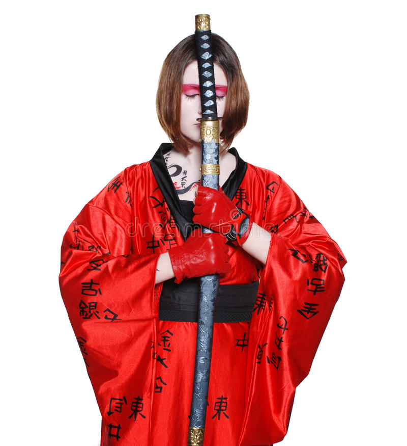 Beautiful warrior girl. Beautiful young geisha girl in kimono with sword on the isolated background royalty free stock image