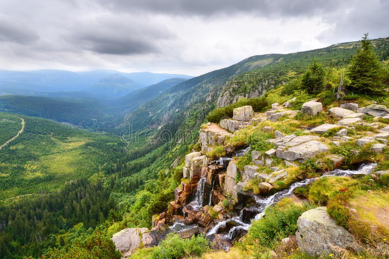 Beautiful waterfall above a deep green valley in the mountains royalty free stock photo