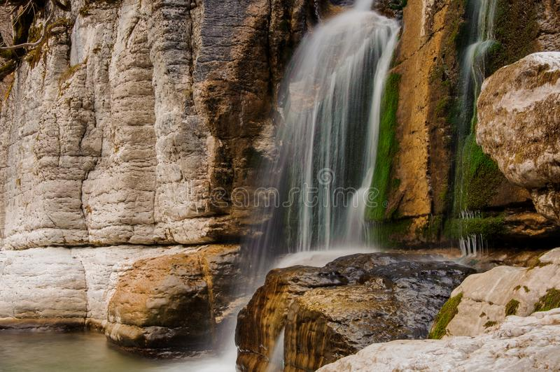 Beautiful waterfall flowing down the high rock in Martvili canyon. Beautiful waterfall flowing down the high rock with moss in Martvili canyon on autumn day royalty free stock photography