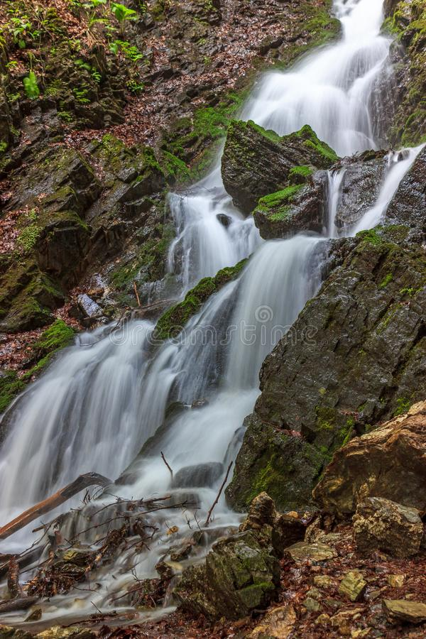 Beautiful waterfall flowing between moss-covered rocks stock photos