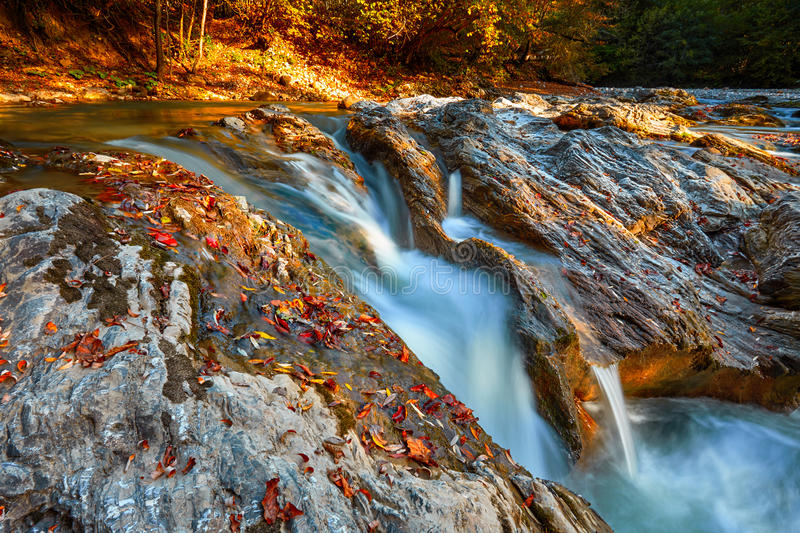 Beautiful waterfall in forest at sunset. Autumn landscape, fallen leaves. Water flow stock photo