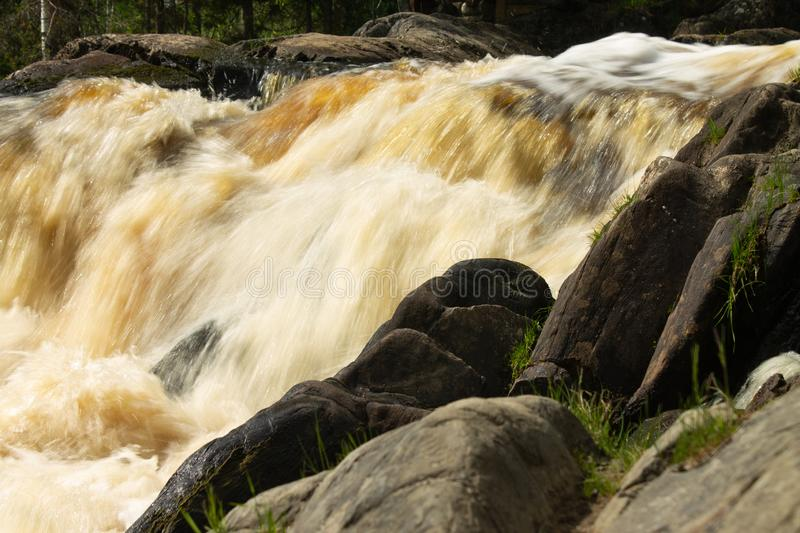 Waterfall over granite rocks fast water flow. Beautiful waterfall landscape on granite stones. fast water flow with blur effect stock photography