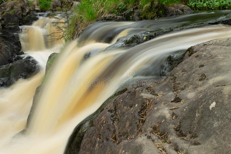 Waterfall over granite rocks fast water flow. Beautiful waterfall landscape on granite stones. fast water flow with blur effect royalty free stock photography