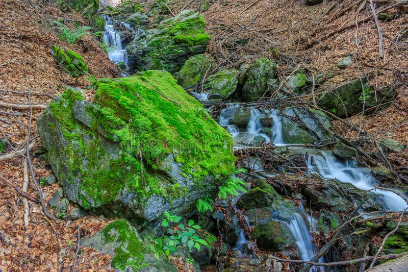 Beautiful waterfall and large  rock covered with moss stock photos
