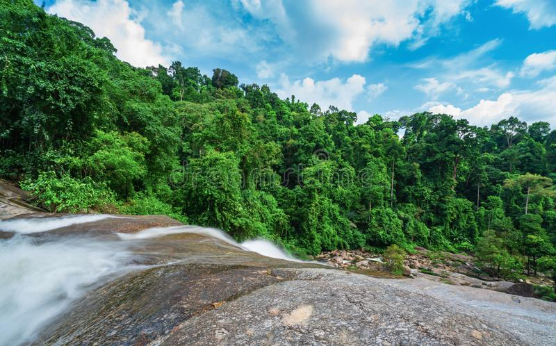 Beautiful waterfall at the mountain with blue sky and white cumulus clouds. Waterfall in tropical green tree forest. Waterfall royalty free stock photo