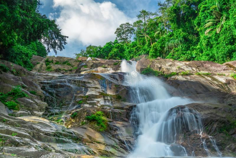 Beautiful waterfall at the mountain with blue sky and white cumulus clouds. Waterfall in tropical green tree forest. Waterfall royalty free stock photography