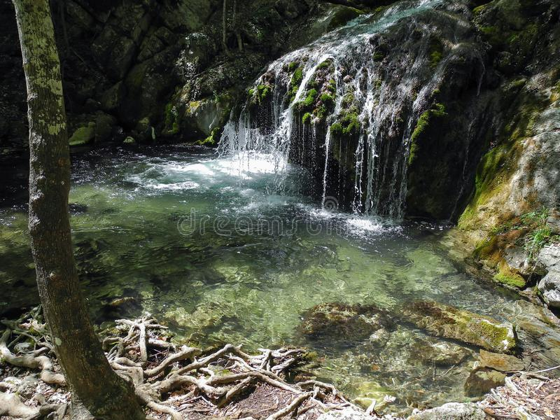 Beautiful waterfall with natural pool in the mountin forest. Exotic cascading river on Crimean mountains at spring, tourist place royalty free stock photo