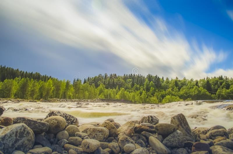 Beautiful waterscape with white moving cloud and waterfall from uphill in majestic outdoor in northern europe royalty free stock photo