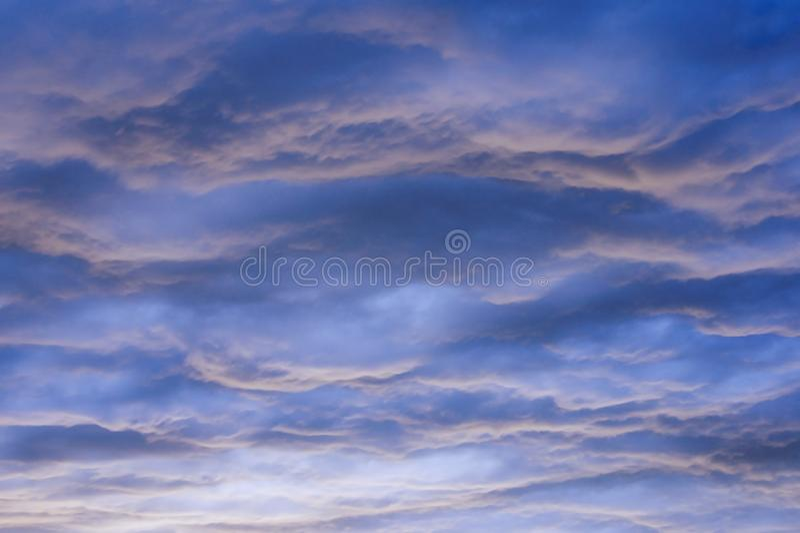 Beautiful wavy cloudy sky at sunset, natural background. Beautiful wavy cloudy sky at sunset, natural blue wavy background stock photos