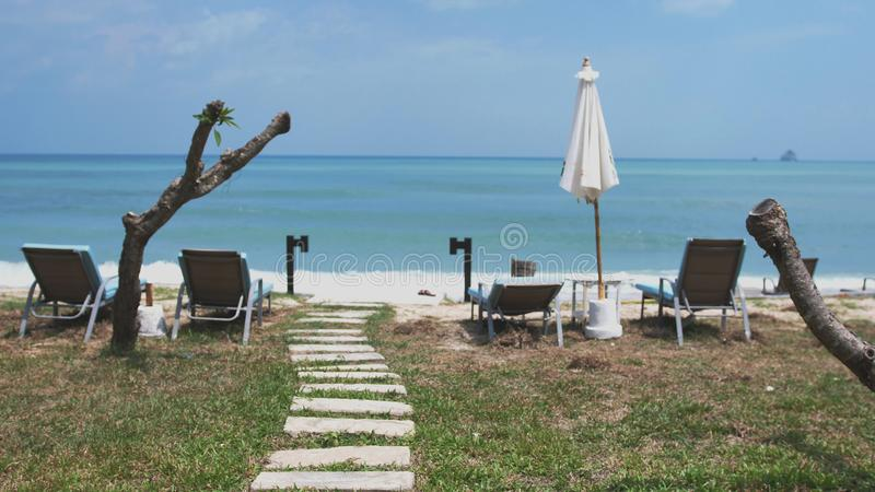 Beautiful way from stones to the ocean beach with umbrellas and sunbeds. stock image