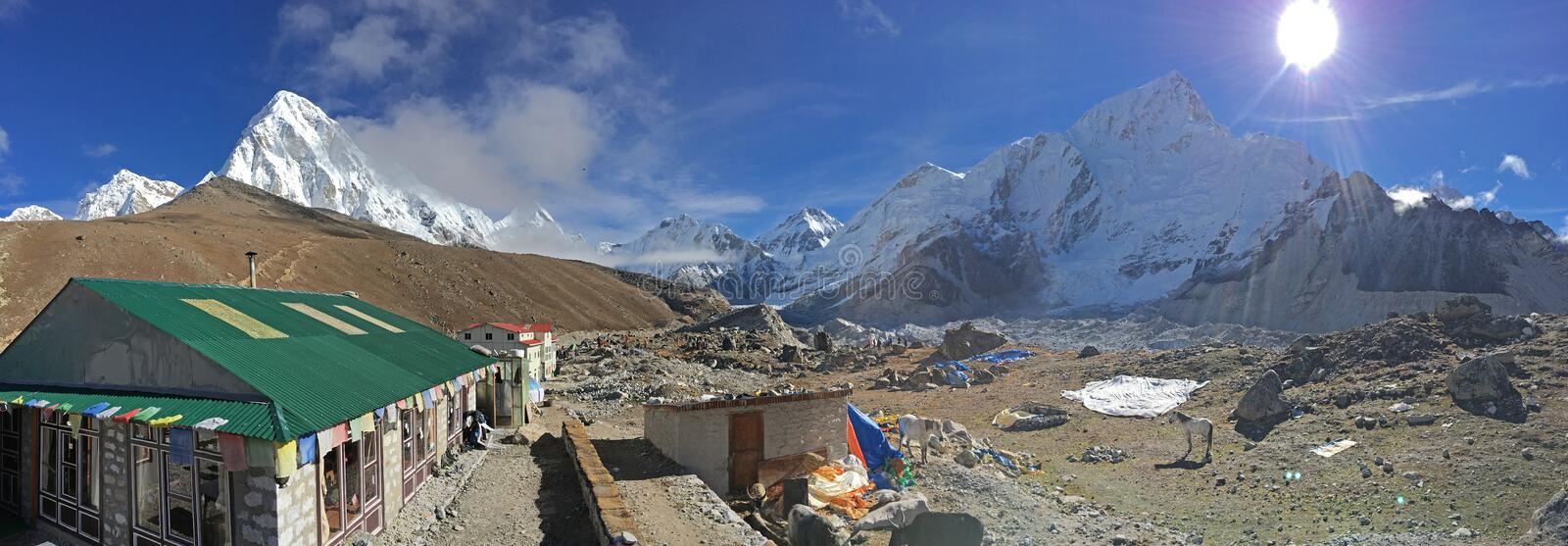 Beautiful weather at Gorak Shep with Nepalese guest houses and snow capped Himalayan range in the background. The sun is shinnig bright and there are horses royalty free stock photography