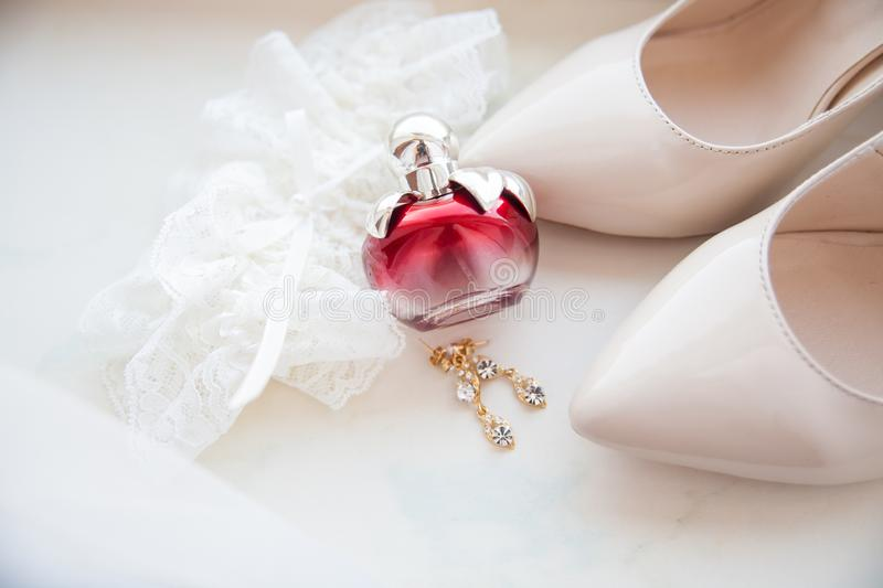 Beautiful wedding accessories. Bride shoes, perfumes on a white veil.  royalty free stock image