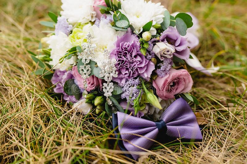 Beautiful wedding bouquet with bow-tie on the grass. Wedding composition stock photos