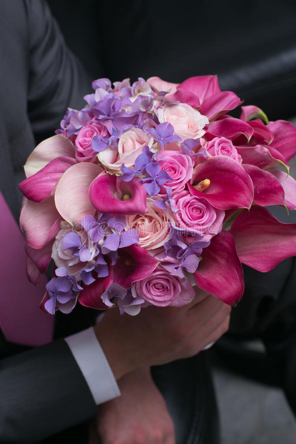 Wedding bouquet for bride in hands of groom royalty free stock photo