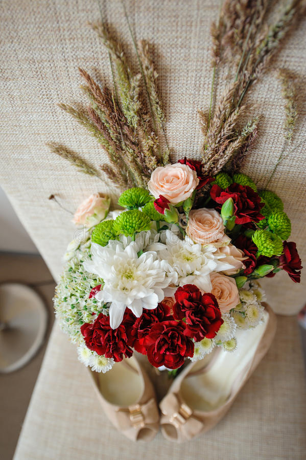 Beautiful wedding bouquet and bride's shoes stock photo