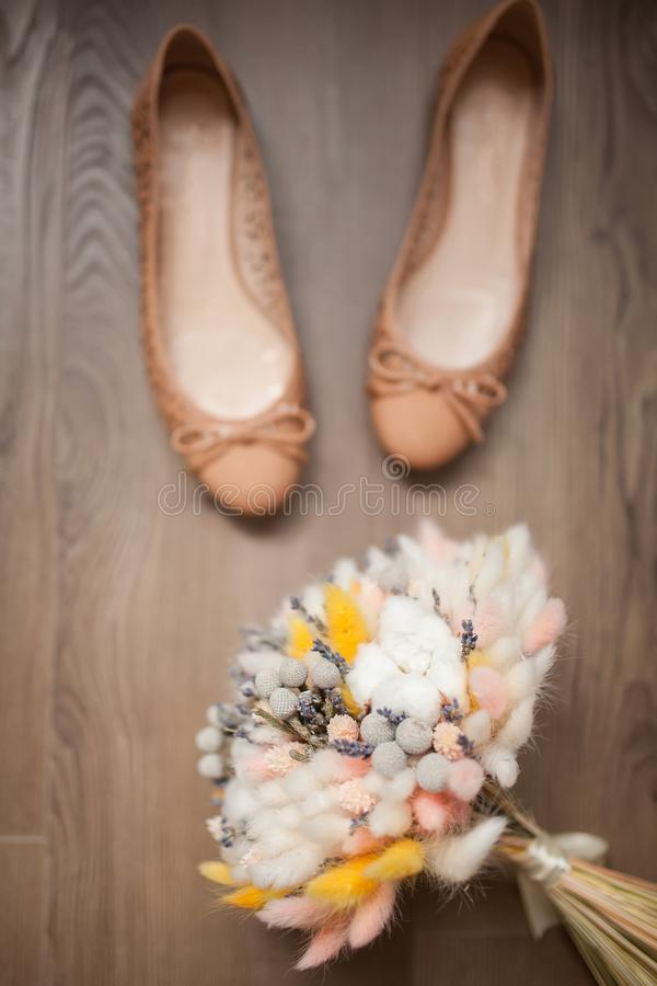 Beautiful wedding bouquet of dry flowers and ballet shoes. royalty free stock images