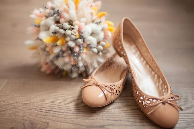 Beautiful wedding bouquet of dry flowers and ballet shoes. Beautiful wedding bouquet of dry flowers and ballet shoes on wooden surface, bride`s morning. Rustic stock photos