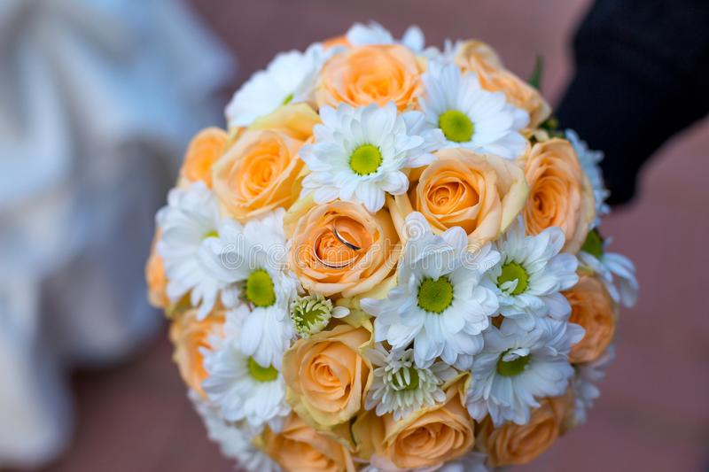 Beautiful wedding bouquet of flowers with wedding rings royalty free stock photos