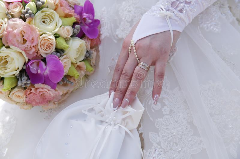 A beautiful wedding bouquet in the hand of the bride and a white handbag with rhinestones in the other hand with a wedding ring on stock photography