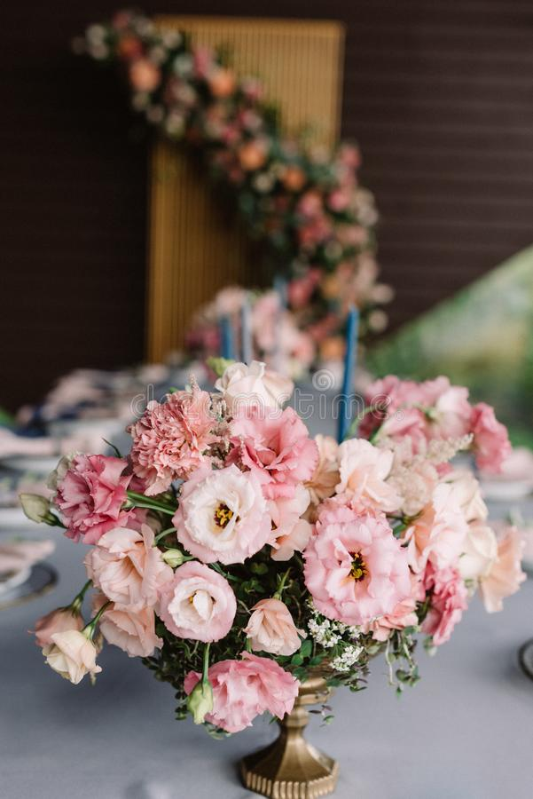The beautiful, wedding bouquet on the holiday table adorns the table for guests. Stylish and wedding flowers in a golden vase stock photography