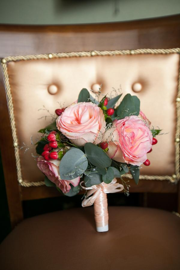 Beautiful wedding bouquet on a luxurious chair, close-up. Bouquet of pink roses, green leaves and buds, tied with satin ribbon, royalty free stock photo