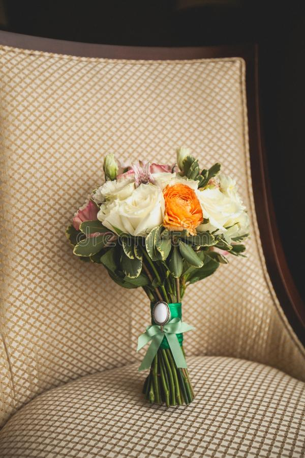 Beautiful wedding bouquet on a luxurious velour chair, close-up. Bouquet of different flowers and green leaves, tied with satin stock images