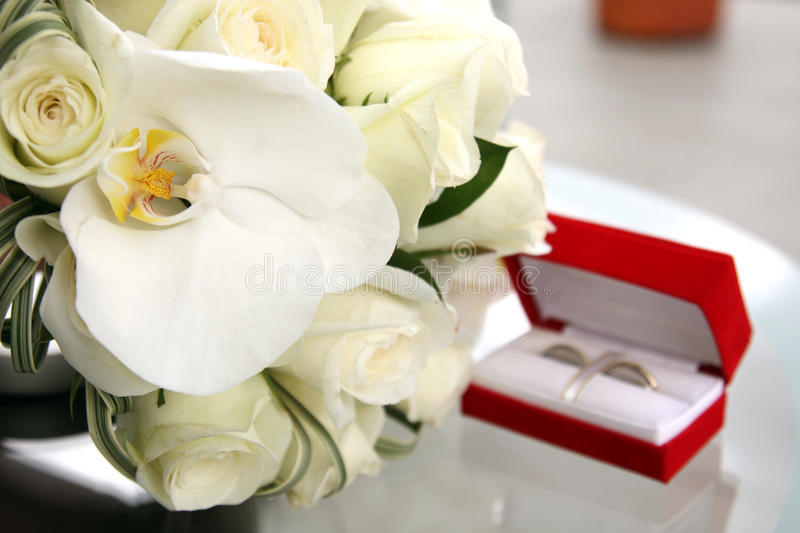Beautiful wedding bouquet of roses and orchids and red velvet box with gold and platinum wedding rings stock photo
