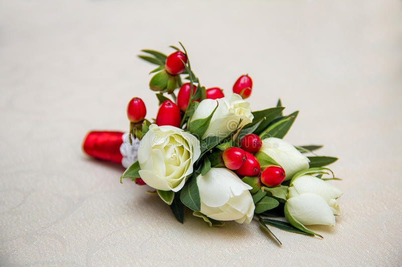 Beautiful wedding boutonniere of varios flowers on white wooden background royalty free stock photos