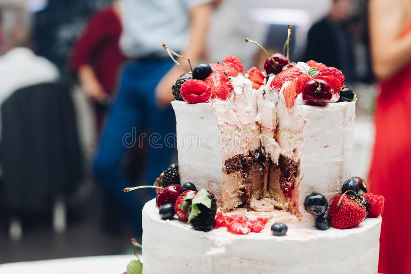 Beautiful wedding cake with berries.Sliced wedding cake in close-up. stock images