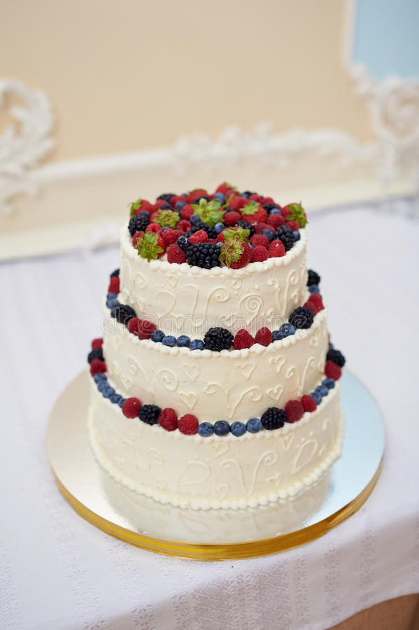 Beautiful wedding cake with berries on wooden table. On light background royalty free stock photography
