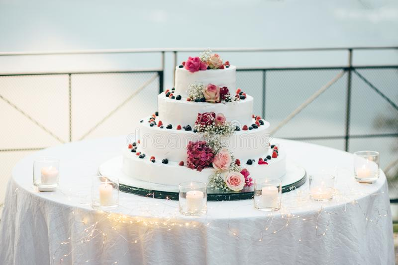 A beautiful wedding cake in four levels is on the table against the background of the picturesque lake royalty free stock photos