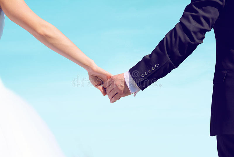 Beautiful wedding couple, bride and groom holding hands looking stock photography