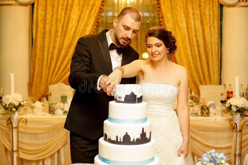 Beautiful wedding couple cutting the wedding cake royalty free stock photos