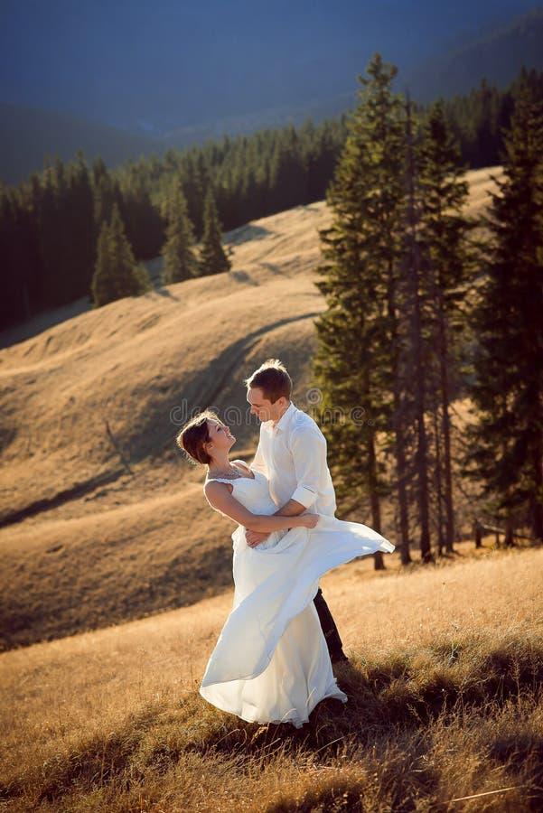 Beautiful wedding couple dances on the mountain peak royalty free stock photos