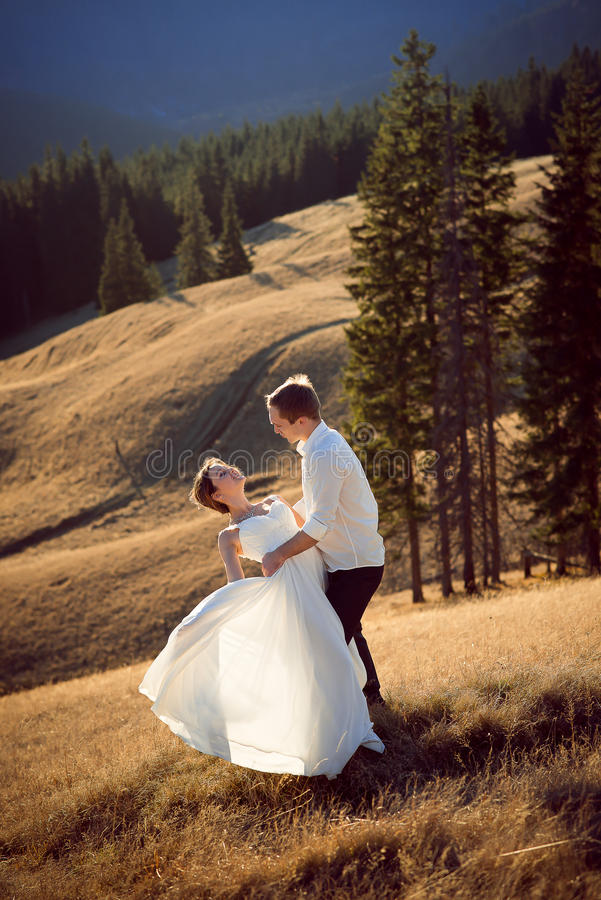 Beautiful wedding couple dances on the mountain peak stock photo