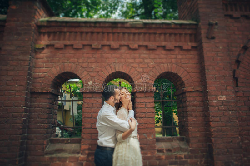 Beautiful wedding couple hugging standing near old building royalty free stock images