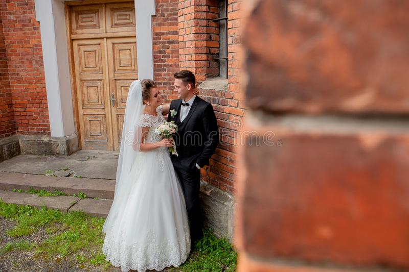 Beautiful wedding couple husband in suit and wife in wedding dress posing near the wall royalty free stock photography