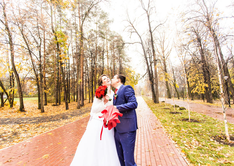 Beautiful Wedding couple kissing in the rain royalty free stock images