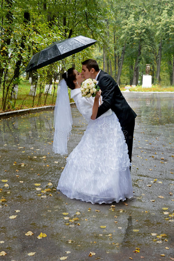 Beautiful wedding couple kissing in the rain. Bride and groom stock image