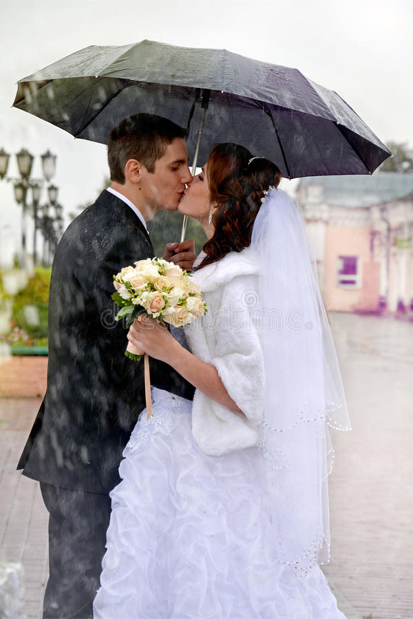 Beautiful wedding couple kissing in the rain. Bride and groom royalty free stock photo