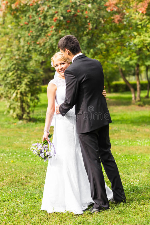Beautiful wedding couple outdoors. They kiss and hug each other stock images