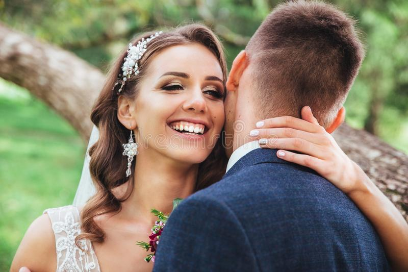 Beautiful wedding couple in park. They kiss and hug each other stock photo