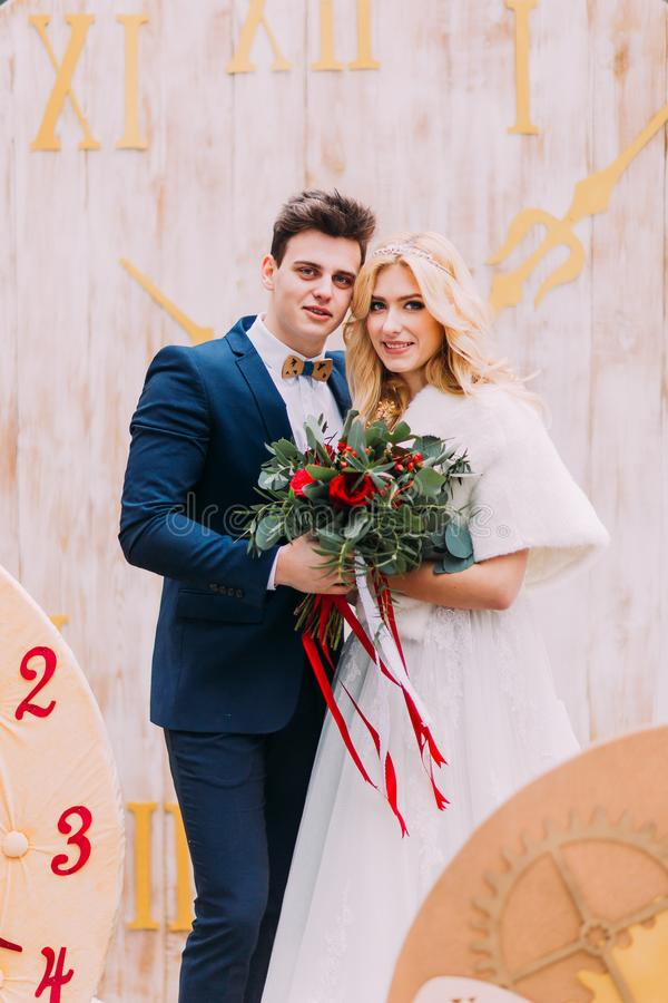 Beautiful wedding couple posing with bouquet of red roses. Creative decorations on background. royalty free stock photography